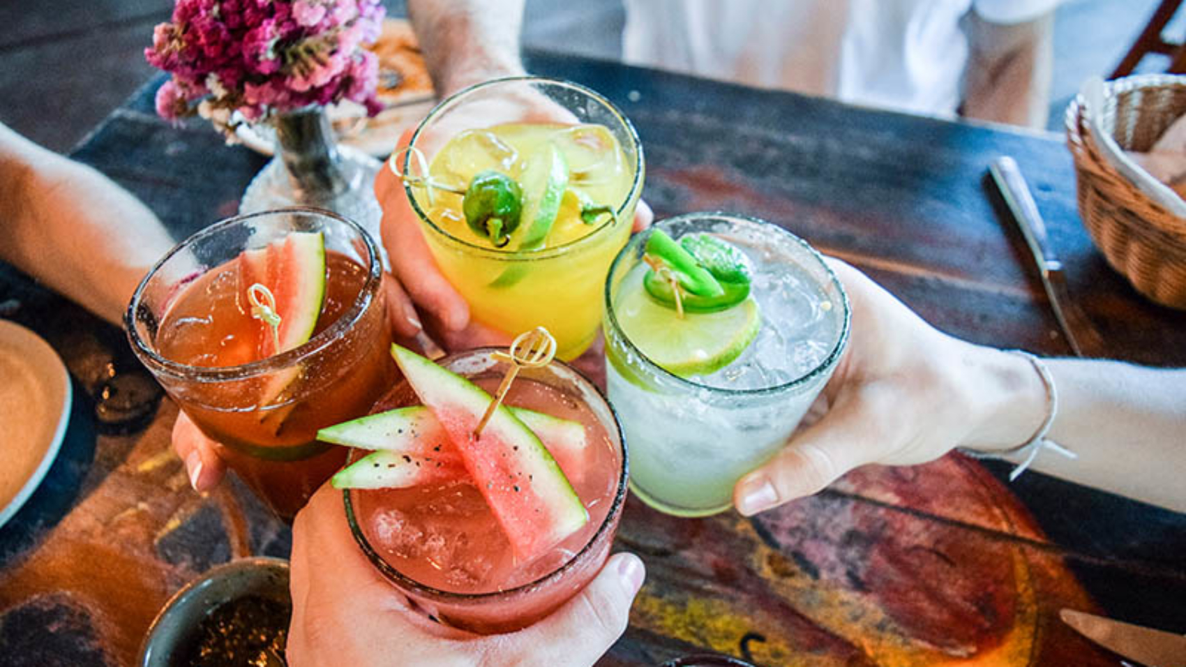 Friends toasting, saying cheers holding tropical blended fruit margaritas.  Watermelon and passionfruit drinks.; Shutterstock ID 780298633